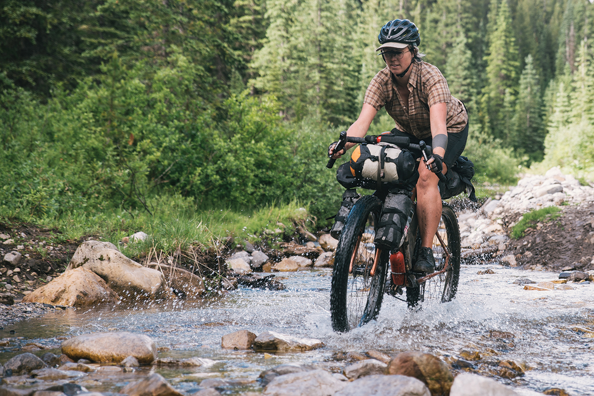 The author navigates a stream along the Great Divide mountain bike route