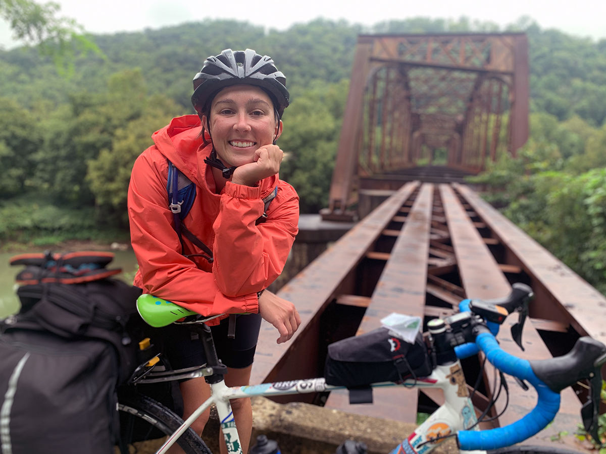 Sydney stands with her bike in rural Kentucky next to a derelict train bridge, a huge smile on her face.