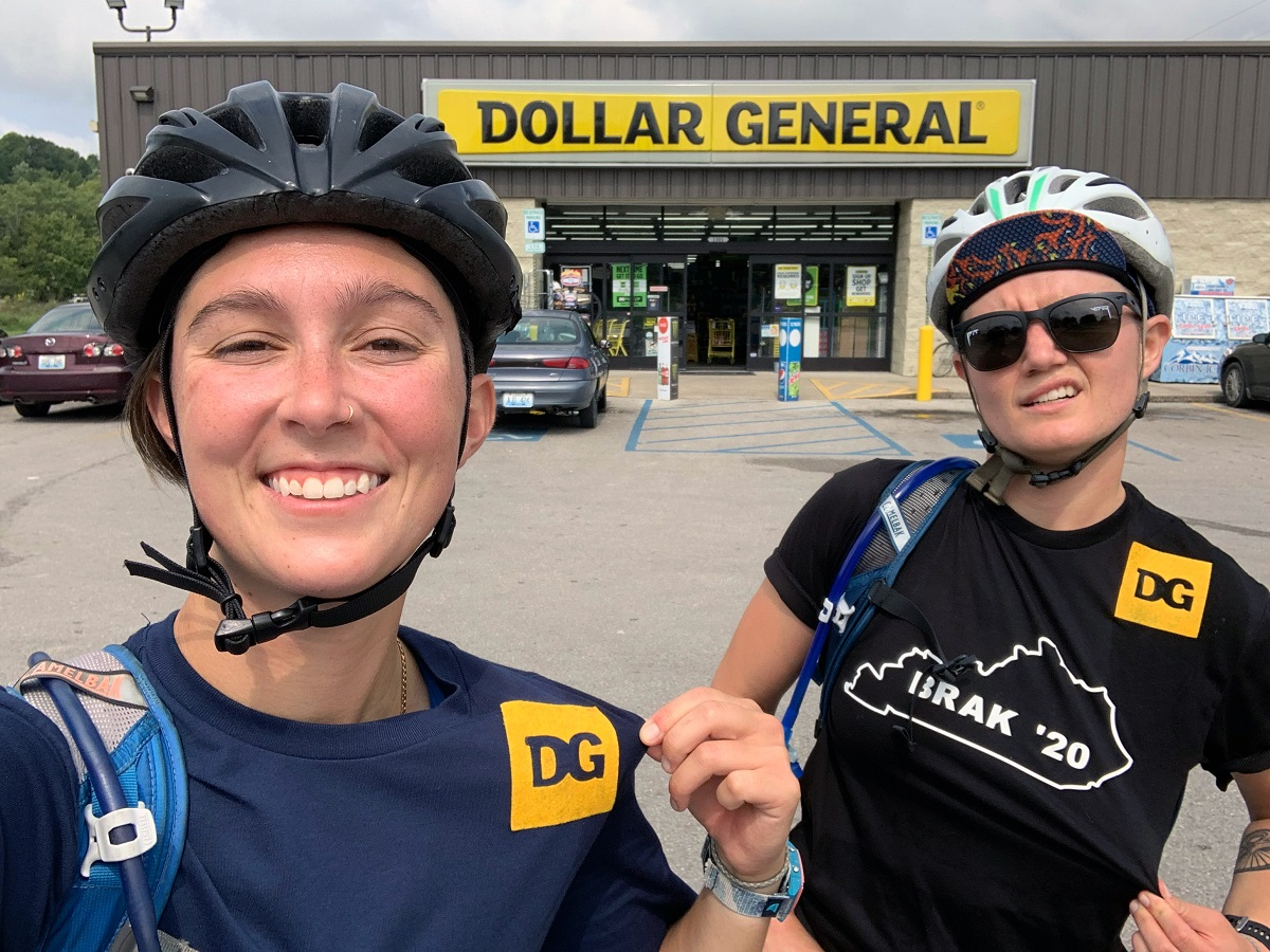 "Sydney and Amanda add DG to their ""cycling kits"" aka their tshirts as they stand in front of a Dollar General store."