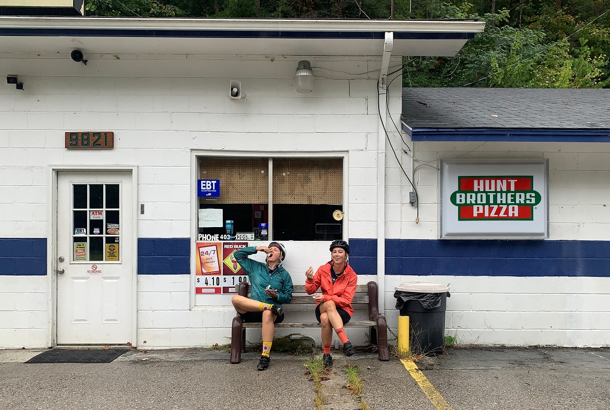 Sydney and Amanda sit in front of a convenience store and chow down on junk food.