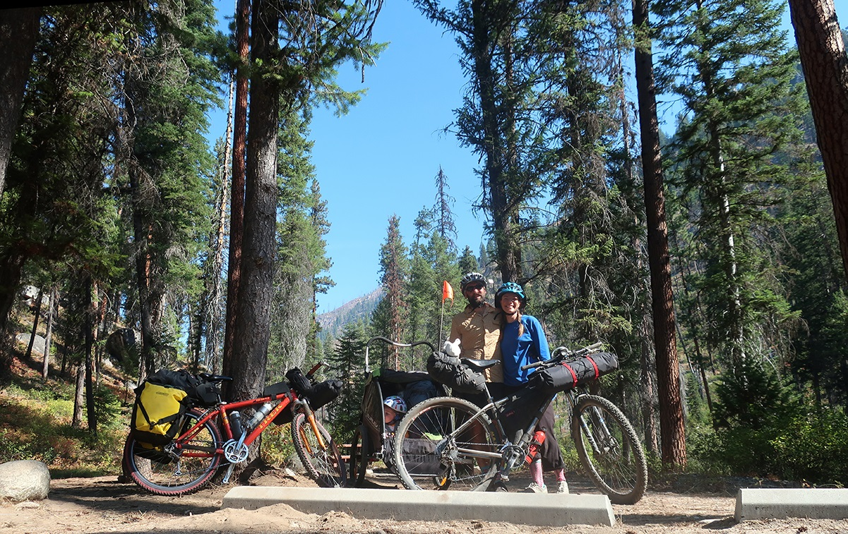 Melissa and her husband stand with their bikes, trailer, and kid in front of a stand of pine trees.
