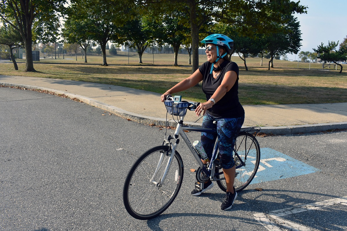 Y.O.U. Executive Director Bernadette Souza stands astride her bike, ready to lead the charge