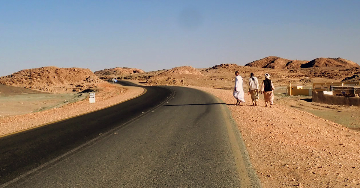 Sudanese men walk along a desert road