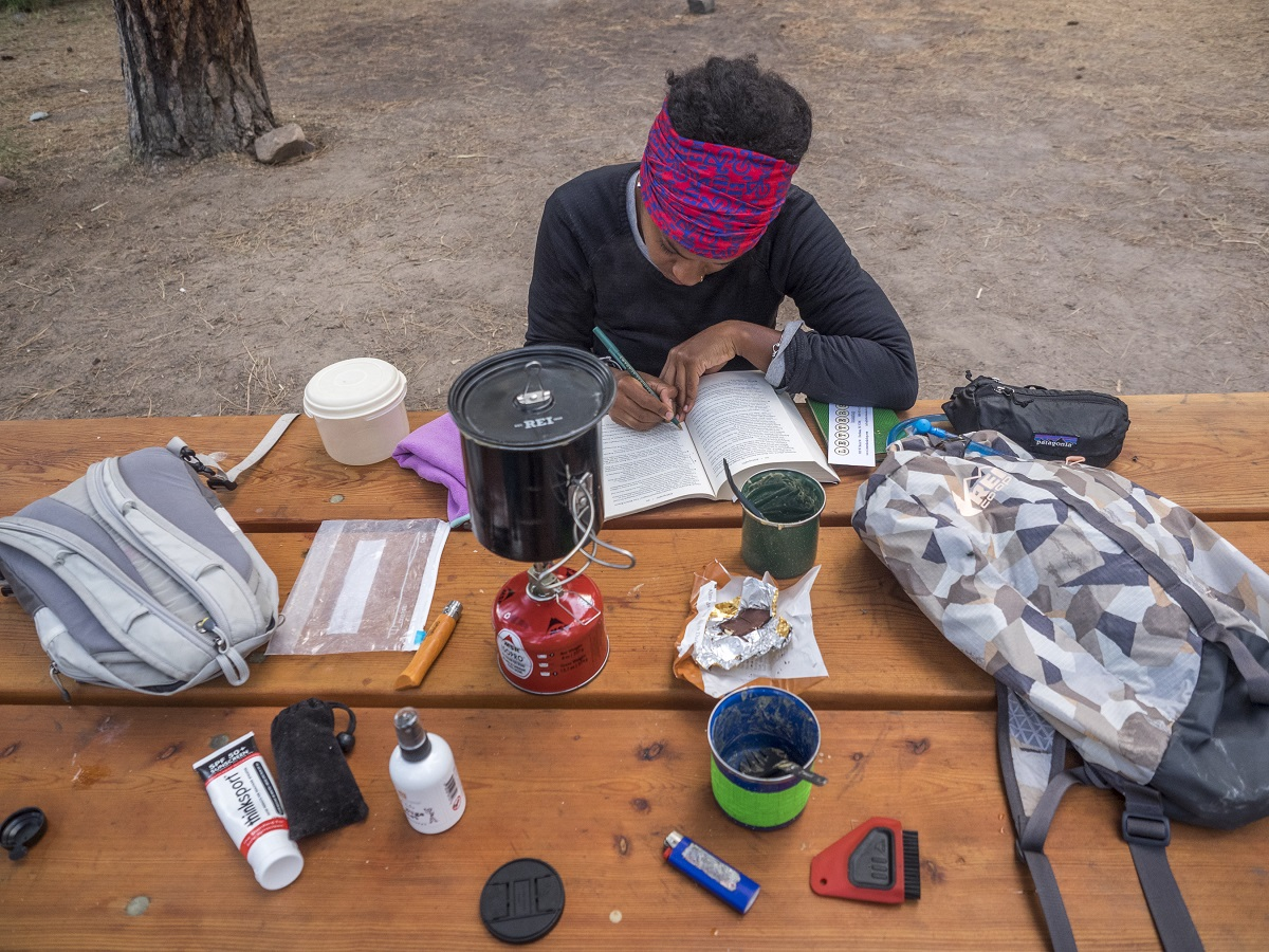 Devin reads at the picnic table while camping on her bikepacking trip in Montana