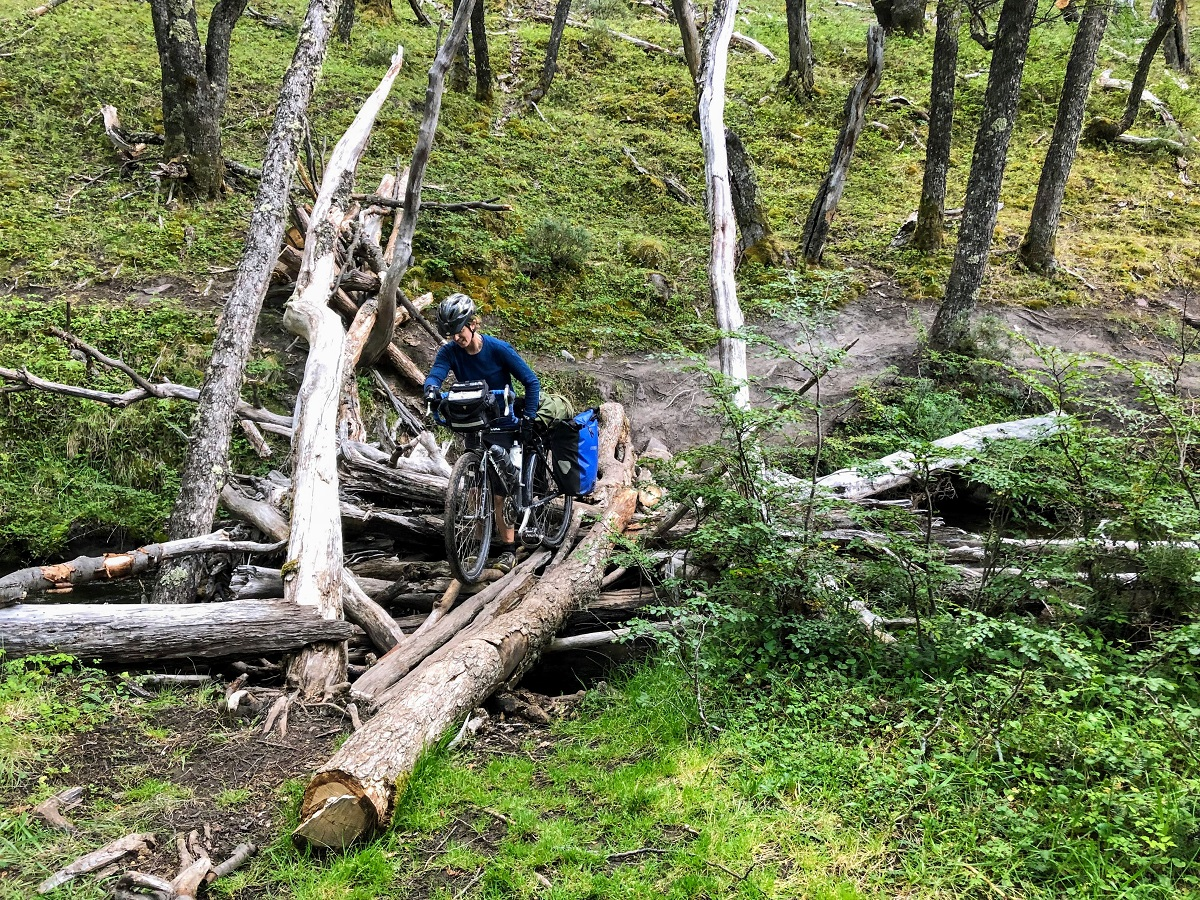 Alissa walks her loaded bicycle across some logs while bikepacking in Chile.