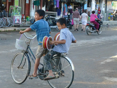 Two children share a bicycle in Myanmar